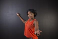 Południe - afrykanin lub amerykanin afrykańskiego pochodzenia kobieta ucznia lub nauczyciela writing na blackboard Obrazy Stock