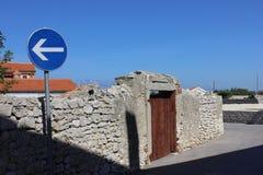 Południowa grodzka ulica z starym kamienia płotowym i drogowym znakiem Obrazy Royalty Free