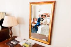 Poślubiać strzał piękny państwa młodzi całowanie obok lustra w pokoju hotelowym Zdjęcia Stock