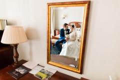 Poślubiać strzał piękny państwa młodzi obsiadanie obok lustra w pokoju hotelowym Fotografia Royalty Free