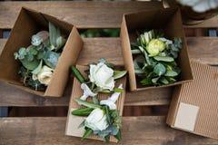 Poślubiać ustawiam boutonnieres róże na drewnianym stole Fotografia Stock
