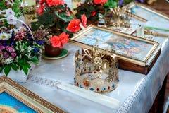 Poślubiać w kościelnych złocistych koronach i kwiatach zdjęcie royalty free