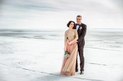 _ Poślubiać zamarzniętym morzem Potomstwa dobierają się w miłości, fornalu i pannie młodej w ślubnej sukni, przy nadmorski Para w Zdjęcia Royalty Free