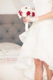Poślubia, małżeństwo bukiet i ślubna suknia Panna młoda w domu Bridal łóżko fotografia stock