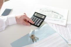 Pośrednik handlu nieruchomościami analizuje pieniężnego planowanie dom Zdjęcie Royalty Free