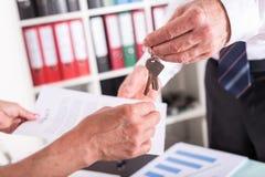 Pośrednik handlu nieruchomościami daje domów kluczom jego klient Zdjęcia Stock