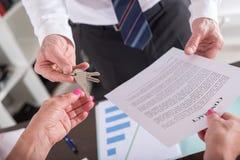 Pośrednik handlu nieruchomościami daje domów kluczom jego klient Obraz Royalty Free