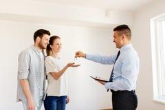 Pośrednik handlu nieruchomościami daje kluczom od nowego domu szczęśliwa para Zdjęcie Royalty Free