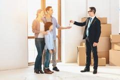 Pośrednik handlu nieruchomościami daje kluczom rodzina w nowym mieszkaniu z kartonami Obraz Stock