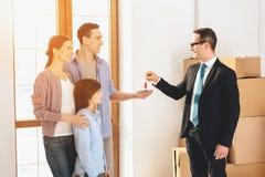 Pośrednik handlu nieruchomościami daje kluczom rodzina w nowym mieszkaniu z kartonami Zdjęcie Royalty Free