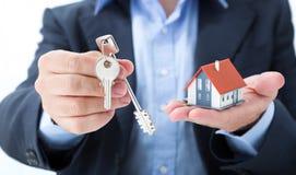 Pośrednik handlu nieruchomościami dostarcza z domowymi kluczami obraz stock