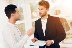 Pośrednik handlu nieruchomościami dyskutuje z klientem warunki dla kupować nieruchomość lub sprzedawać Obrazy Stock
