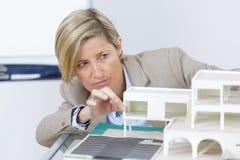 Pośrednik handlu nieruchomościami kobieta przegląda szalkowego modela domy zdjęcia stock