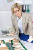 Pośrednik handlu nieruchomościami kobieta przegląda szalkowego modela domy obraz stock