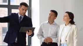 Pośrednik handlu nieruchomościami pokazuje biuro klienci z pastylka komputerem osobistym zbiory