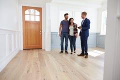 Pośrednik handlu nieruchomościami Pokazuje Latynoskiej pary Wokoło Nowego domu Fotografia Royalty Free