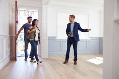 Pośrednik handlu nieruchomościami Pokazuje Latynoskiej pary Wokoło Nowego domu Obrazy Royalty Free