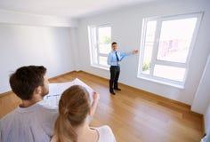 Pośrednik handlu nieruchomościami pokazuje nowego dom para z projektem Zdjęcia Royalty Free