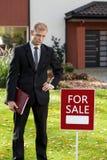 Pośrednik handlu nieruchomościami pozycja przed domem Zdjęcie Royalty Free