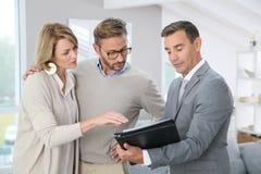Pośrednik handlu nieruchomościami przedstawia kontrakt klienci Obrazy Stock