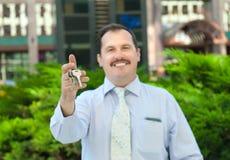 Pośrednik handlu nieruchomościami trzyma out klucze Obraz Royalty Free