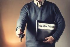 Pośrednik handlu nieruchomościami w pustym mieszkaniu daje kluczom i trzyma czarną falcówkę z kontraktami Pośrednik handlu nieruc Obraz Stock