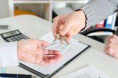 Pośrednik handlu nieruchomościami wręcza klucze jego klient Fotografia Stock