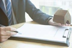 Pośrednik handlu nieruchomościami wyjaśnia hipoteczną pożyczkową zgodę jego klient Real est Fotografia Stock
