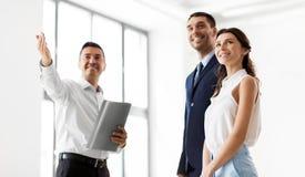 Pośrednik handlu nieruchomościami z falcówką pokazuje klientom nowego biuro Zdjęcie Stock