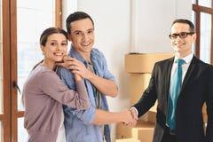 Pośrednik handlu nieruchomościami z rodziną w nowym mieszkaniu z kartonami Mąż i pośrednik handlu nieruchomościami trząść ręki Zdjęcia Stock