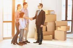 Pośrednik handlu nieruchomościami z rodziną w nowym mieszkaniu z kartonami Ojciec i pośrednik handlu nieruchomościami trząść ręki Fotografia Stock