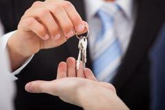 Pośrednik w handlu nieruchomościami daje domów kluczom mężczyzna Zdjęcia Stock