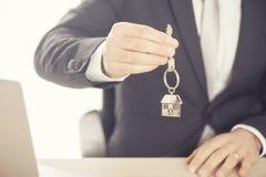 Pośrednik w handlu nieruchomościami daje domowym kluczom na osrebrza dom kształtującego keychain Obrazy Royalty Free