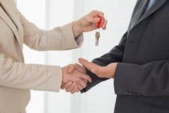 Pośrednik w handlu nieruchomościami daje domu kluczowi klient Zdjęcie Stock
