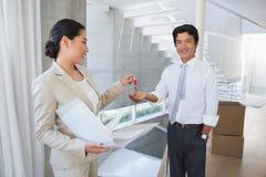 Pośrednik w handlu nieruchomościami daje domu kluczowi nabywca Fotografia Stock