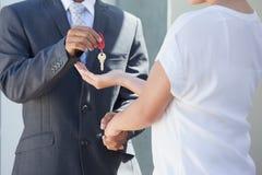 Pośrednik w handlu nieruchomościami daje domu kluczowi nabywca Zdjęcie Royalty Free