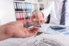 Pośrednik w handlu nieruchomościami daje kluczom jego klient Fotografia Stock