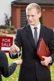 Pośrednik w handlu nieruchomościami daje kluczom klient Fotografia Stock