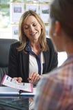 Pośrednik W Handlu Nieruchomościami Dyskutuje własność Z klientem W biurze Obrazy Stock