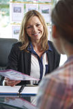 Pośrednik W Handlu Nieruchomościami Dyskutuje własność Z klientem W biurze Fotografia Stock