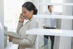 Pośrednik w handlu nieruchomościami opowiada na telefonie z nabywcą w tle Zdjęcie Stock