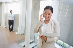 Pośrednik w handlu nieruchomościami opowiada na telefonie z nabywcą w tle Obrazy Royalty Free