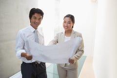 Pośrednik w handlu nieruchomościami patrzeje projekt z potencjalną nabywcą Zdjęcia Stock
