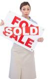 Pośrednik w handlu nieruchomościami pokazuje dla sprzedaż znaka z sprzedającym majcherem przez je Fotografia Royalty Free