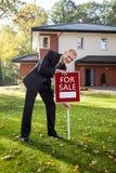 Pośrednik w handlu nieruchomościami próbuje sprzedawać dom Obrazy Royalty Free