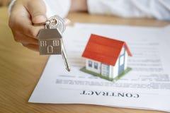 Pośrednik w handlu nieruchomościami wręcza nad domowymi kluczami zdjęcie stock