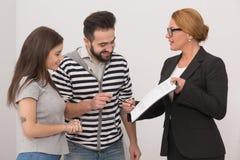 Pośrednik w handlu nieruchomościami wskazuje miejsce w zakup zgodzie dokąd nowi właściciele muszą stawiać podpis Zdjęcie Royalty Free