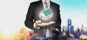 Pośrednika handlu nieruchomościami biznesmen z domu modelem na ręce, z miastowym miasto widokiem w wschodu słońca tle Zdjęcie Stock