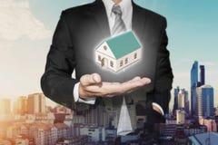Pośrednika handlu nieruchomościami biznesmen z domu modelem na ręce, z miastowym miasto widokiem w wschodu słońca tle Fotografia Stock