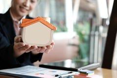 Pośrednika handlu nieruchomościami mienia domu model przy biurem agenta nieruchomości seans Obraz Royalty Free